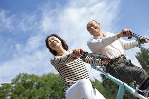 自転車に乗る笑顔の中高年夫婦の写真素材 [FYI01285372]