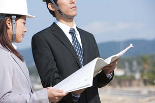 設計図を持っているビジネスウーマンとビジネスマンの写真素材 [FYI01285550]