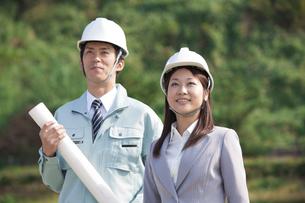 設計図を持っている男性作業員とビジネスウーマンの写真素材 [FYI01285711]