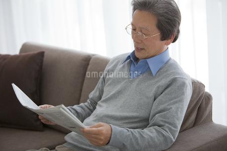 新聞を読む笑顔の中高年男性の写真素材 [FYI01285784]