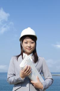 ヘルメットを被って設計図を持っているビジネスウーマンの写真素材 [FYI01285838]