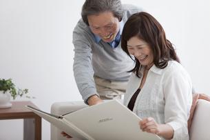アルバムを見る笑顔の中高年夫婦の写真素材 [FYI01285857]