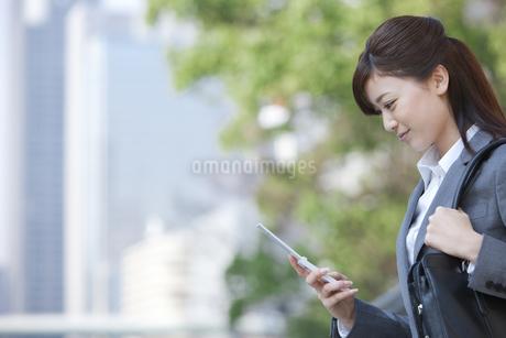 携帯電話を見てほほえむビジネスウーマンの写真素材 [FYI01285863]
