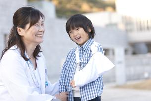 笑顔の女性医師と腕を怪我している男の子の写真素材 [FYI01285892]