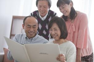 アルバムを見る笑顔の中高年4人の写真素材 [FYI01285966]