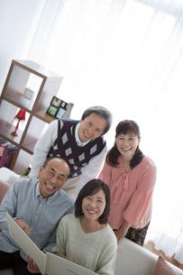 ソファーに座ってアルバムを指差す中高年4人の写真素材 [FYI01286000]