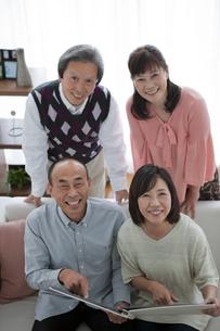 ソファーに座ってアルバムを指差す中高年4人の写真素材 [FYI01286029]