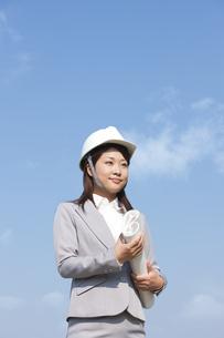 ヘルメットを被って設計図を持っているビジネスウーマンの写真素材 [FYI01286110]