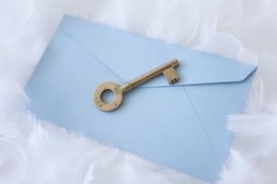 羽の上に置かれた封筒と鍵の写真素材 [FYI01286162]