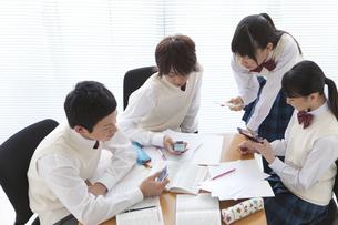 携帯電話を見ている男女中高生4人の写真素材 [FYI01286255]