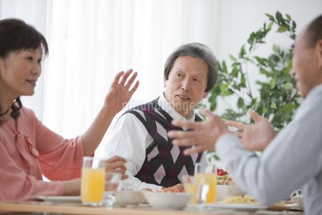 ホームパーティーをする中高年3人の写真素材 [FYI01286786]