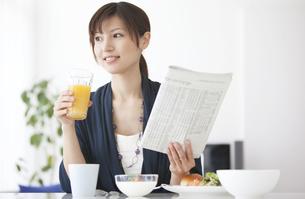 グラスと新聞を持っている女性の写真素材 [FYI01287152]