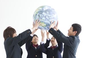 地球のボールを持っている男女中高生4人の写真素材 [FYI01287166]