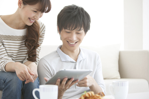 タブレットPCを見ているカップルの写真素材 [FYI01287229]