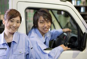 軽トラックに乗っている作業着姿の男性と女性の写真素材 [FYI01287334]
