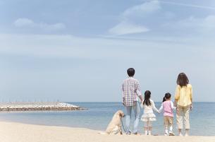 海を眺めている家族と犬の後姿の写真素材 [FYI01287359]