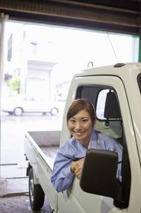 軽トラックに乗っている作業着姿の女性の写真素材 [FYI01287365]