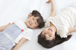 寝転んでいる女の子2人の写真素材 [FYI01287416]