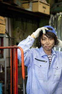 帽子を被る作業着姿の若者男性の写真素材 [FYI01287478]