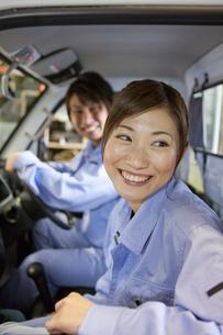 軽トラックに乗っている作業着姿の男女の写真素材 [FYI01287481]