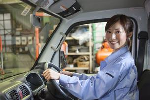 軽トラックに乗っている作業着姿の女性の写真素材 [FYI01287491]