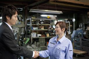 握手するスーツの男性と作業着姿の女性の写真素材 [FYI01287616]