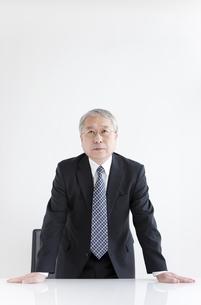 机に手をつく中高年ビジネスマンの写真素材 [FYI01287648]
