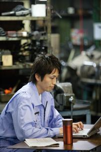 パソコンを操作する作業着姿の男性の写真素材 [FYI01287680]