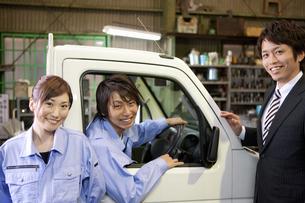 笑顔のスーツの男性と作業着姿の男女の写真素材 [FYI01287741]