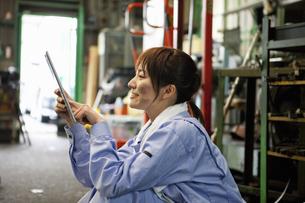 タブレットPCを操作する作業着姿の若者女性の写真素材 [FYI01287771]