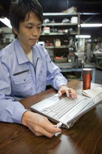 USBメモリを差し込む作業着姿の男性の写真素材 [FYI01287774]