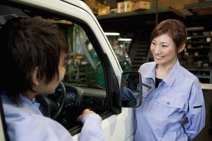 軽トラックに乗っている作業着姿の男性と女性の写真素材 [FYI01287823]