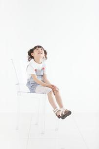 イスに座って見上げている女の子の写真素材 [FYI01287837]