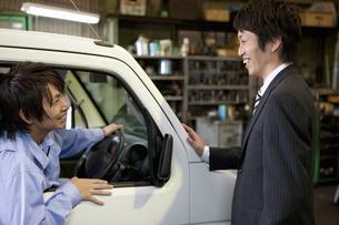 笑顔のスーツの男性と作業着姿の男性の写真素材 [FYI01287987]