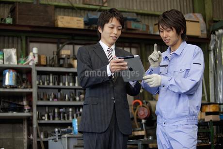 タブレットPCを見せるスーツの男性と作業着姿の男性の写真素材 [FYI01287988]