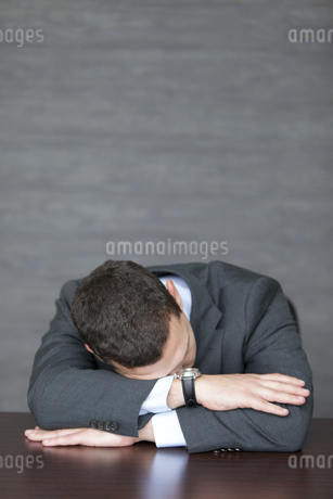 机に伏せる外国人ビジネスマンの写真素材 [FYI01288020]