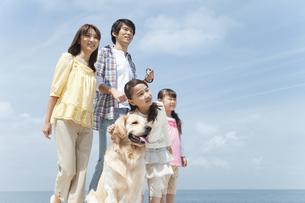 遠くを見ている笑顔の家族と犬の写真素材 [FYI01288109]