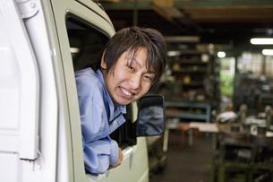 軽トラックに乗っている作業着姿の男性の写真素材 [FYI01288120]
