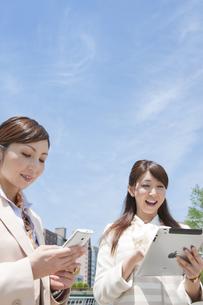 スマートフォンとタブレットPCを操作するビジネスウーマン2人の写真素材 [FYI01288311]