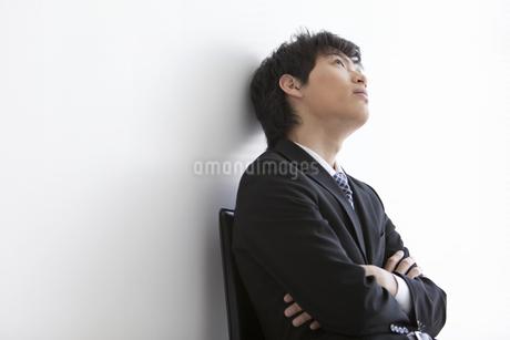 腕組みをして見上げているビジネスマンの写真素材 [FYI01288368]