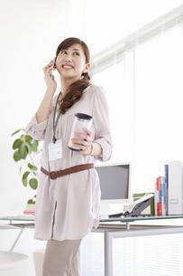 スマートフォンで話しているビジネスウーマンの写真素材 [FYI01288447]