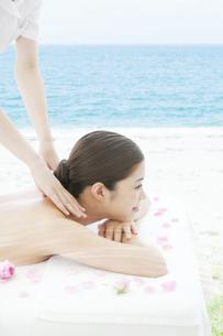 海辺でマッサージを受ける女性の写真素材 [FYI01288455]