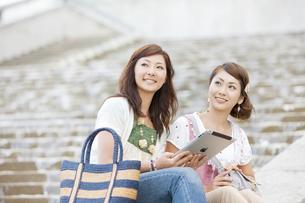 上を見上げる笑顔の女性2人の写真素材 [FYI01288536]