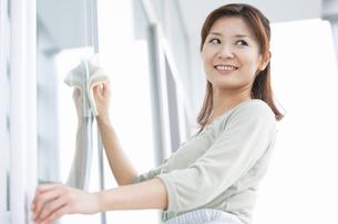 窓ふきする笑顔の女性の写真素材 [FYI01288542]