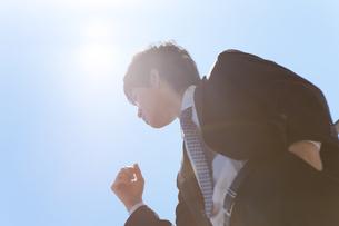 青空の下に立っているビジネスマンの写真素材 [FYI01288569]