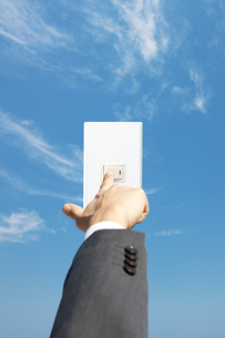 スイッチを押すビジネスマンの手と青空の写真素材 [FYI01288613]