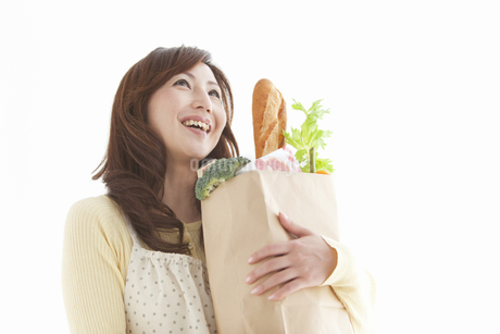 買い物袋を抱えているエプロン姿の女性の写真素材 [FYI01288894]