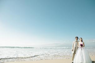 砂浜にたたずむ新郎新婦の写真素材 [FYI01289034]