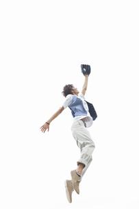 ジャンプしてボールをキャッチする男性の写真素材 [FYI01289283]