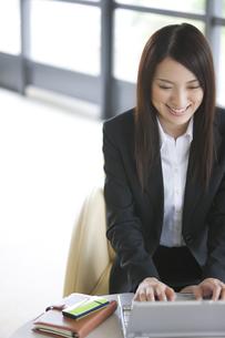 ノートパソコンを操作する笑顔のビジネスウーマンの写真素材 [FYI01289335]